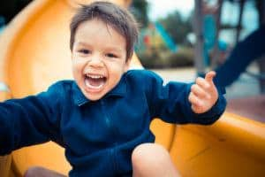 happy young boy on slide at park